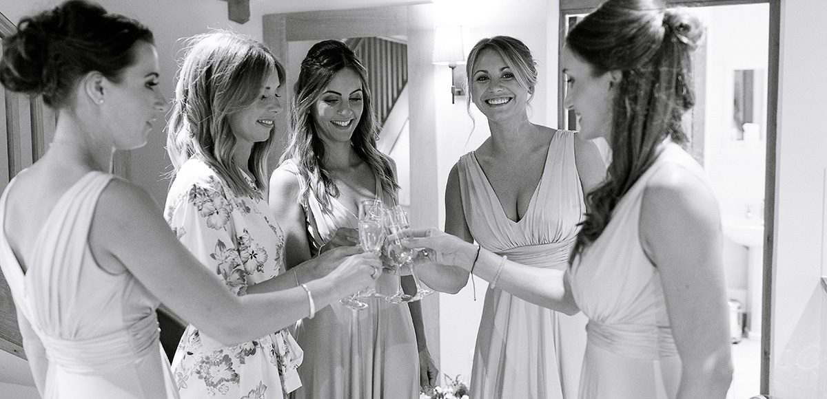 The bridal party celebrate as they prepare for the wedding day in the Apple Loft at Gaynes Park