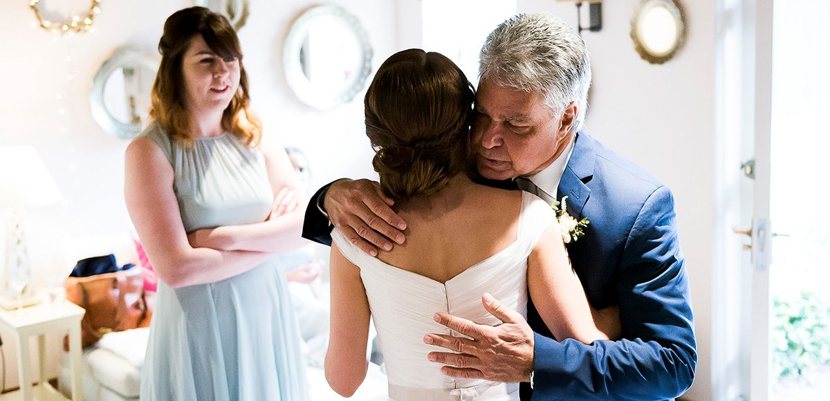 The father of the bride sees his daughter for the first time on her wedding day at Gaynes Park