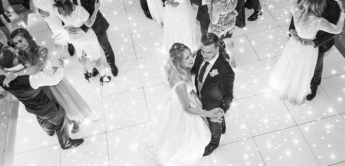 Guests join the newlyweds during their first dance in the Mill Barn at Gaynes Park in Essex