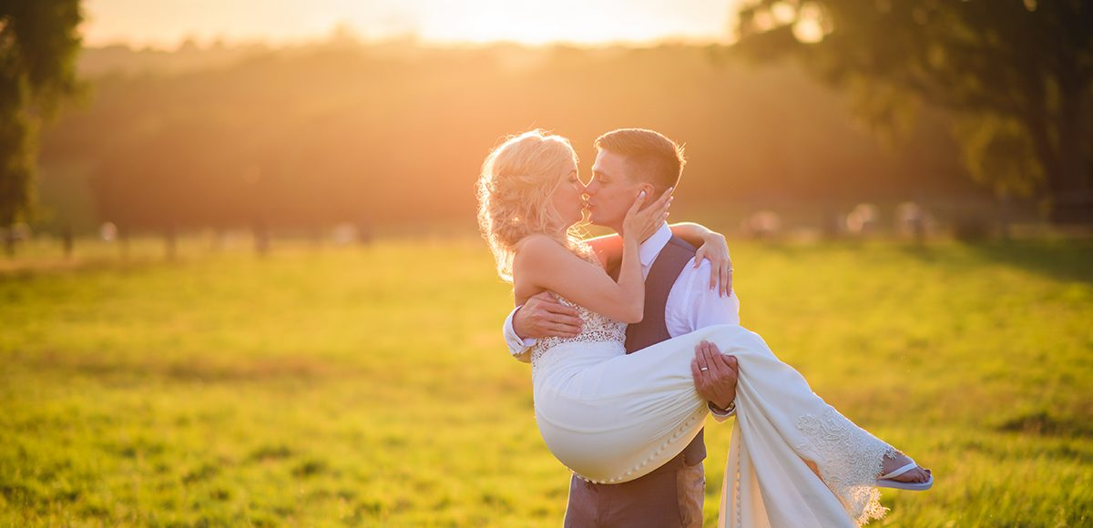 Newlyweds make the most of the golden hour in the countryside that surround Gaynes Park in Essex