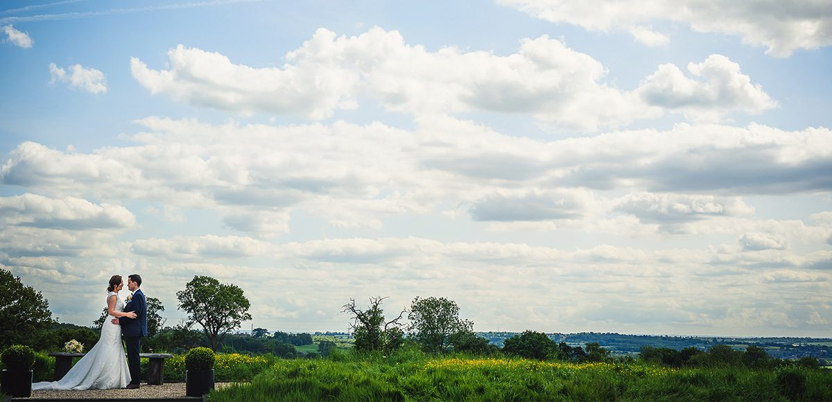 Newlyweds make the most of the London skyline that you can see in the distance at Gaynes Park in Essex