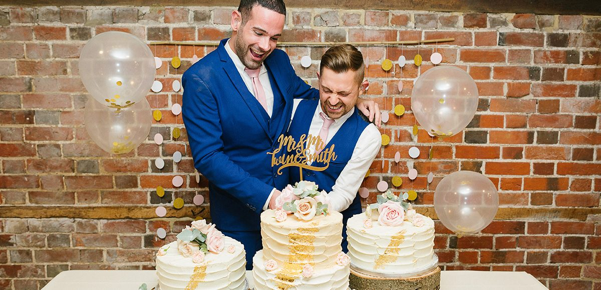 Newlyweds cut their wedding cake in the Mill Barn at Gaynes Park in Essex