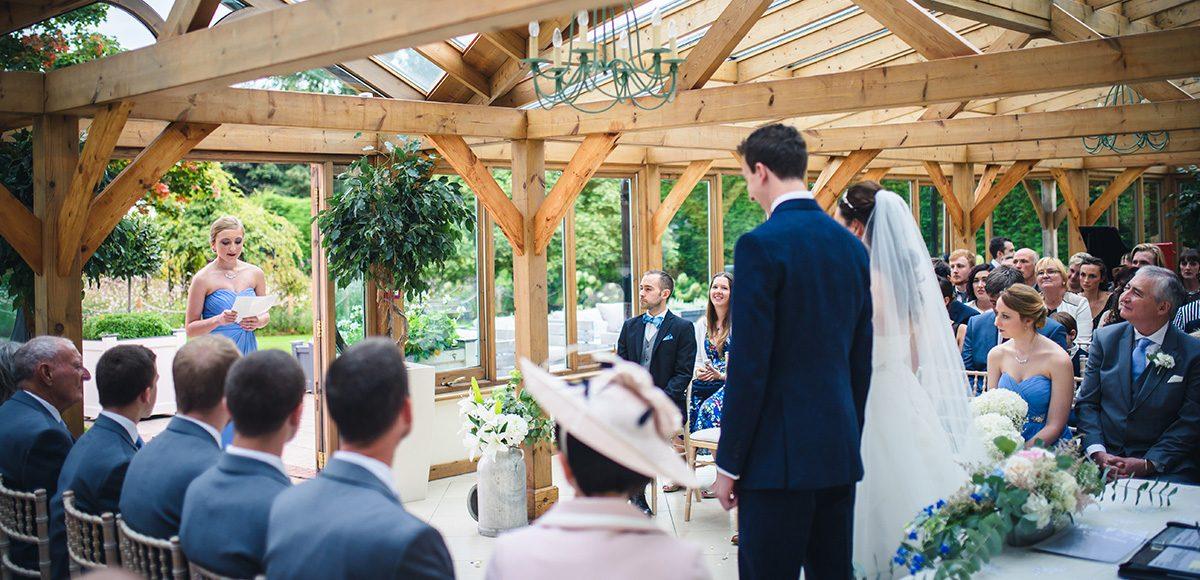 Guests enjoy a wedding ceremony in the Orangery at Gaynes Park wedding venue in Essex