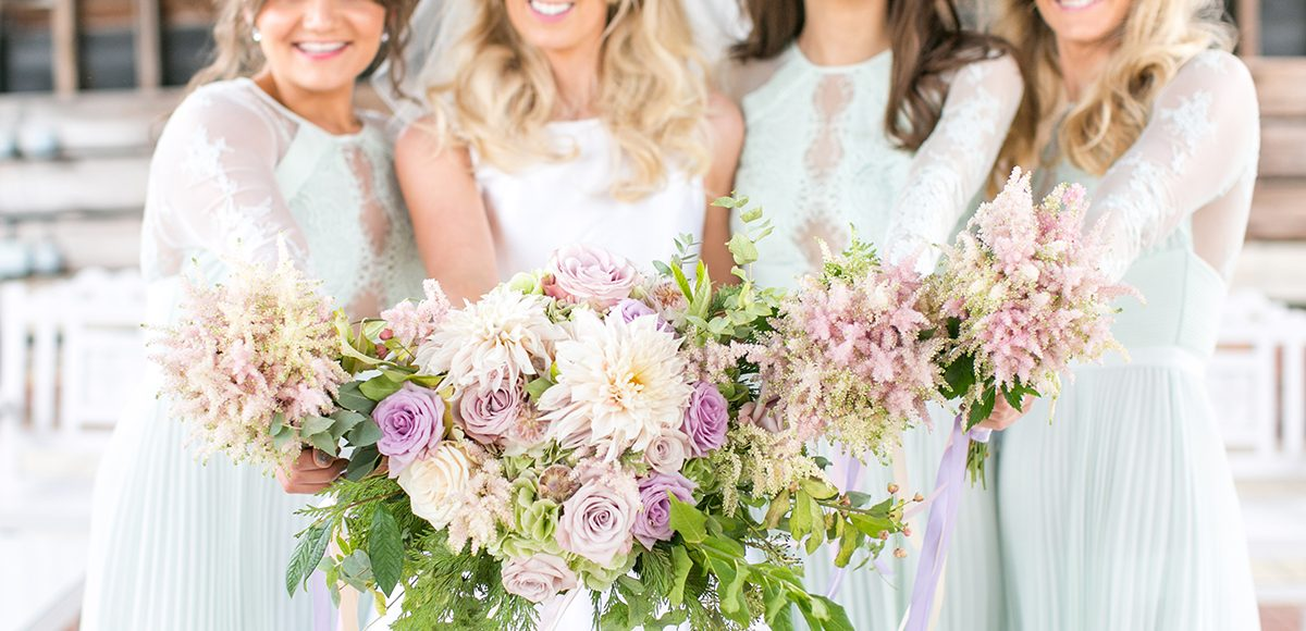The beautiful bride and her bridesmaids stand with their wedding bouquets in the Gather Barn at Gaynes Park