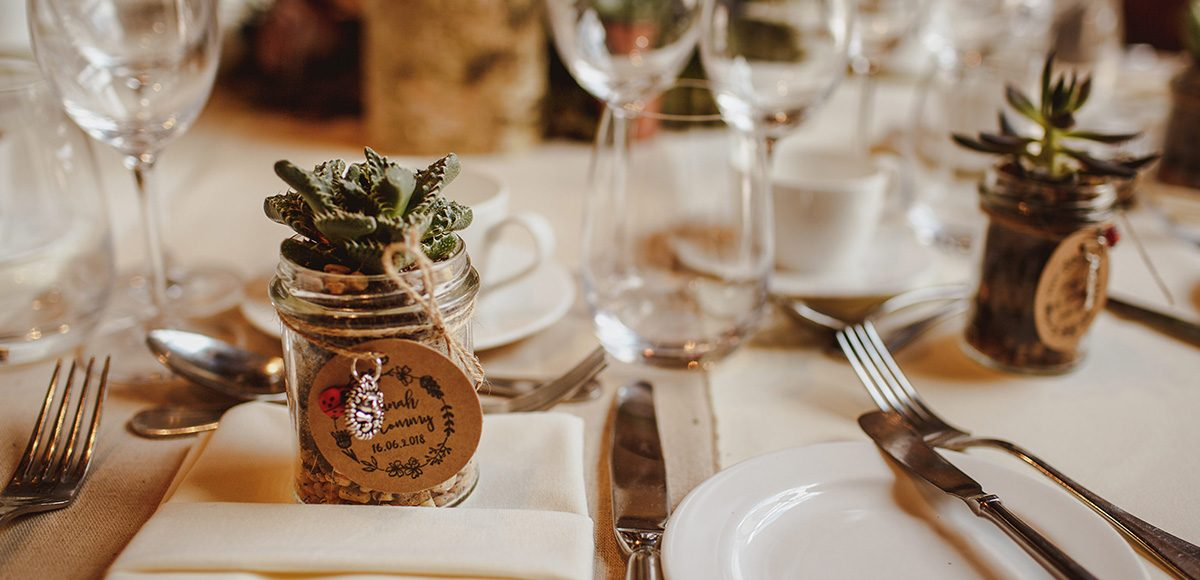 A couple gave jars filled with succulents as wedding favours for their wedding reception at Gaynes Park in Essex