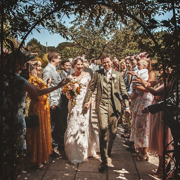 The bride and groom are showered in wedding confetti after their wedding ceremony at Gaynes Park