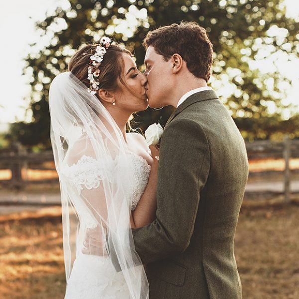 The bride and groom share a kiss as they explore the gardens and grounds at Gaynes Park wedding venue in Essex