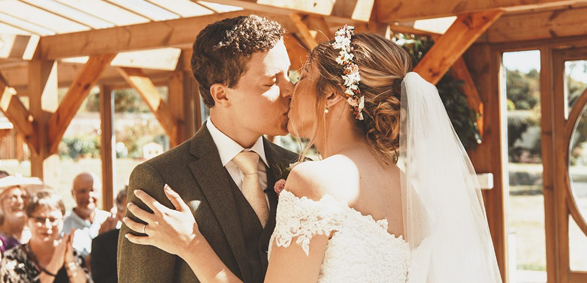 The bride and groom share a kiss during their wedding ceremony in the Orangery at Gaynes Park