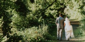 A bride and groom walk through the woodland at Gaynes Park after their woodland wedding ceremony