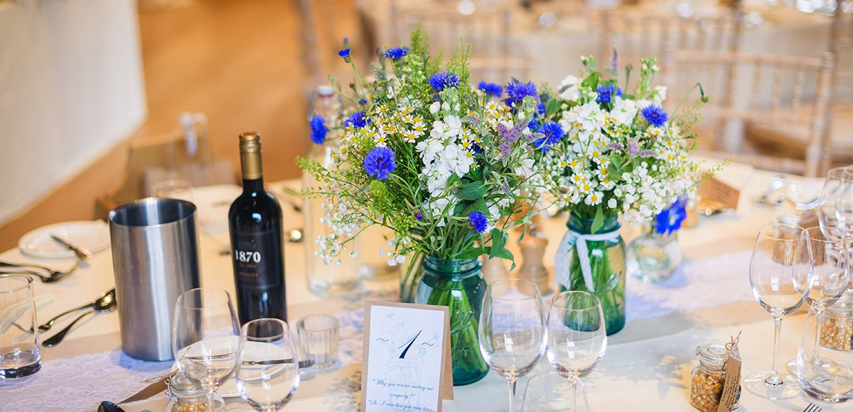 Bright spring flowers add a pop of colour to a table centrepiece in the Mill Barn at Gaynes Park