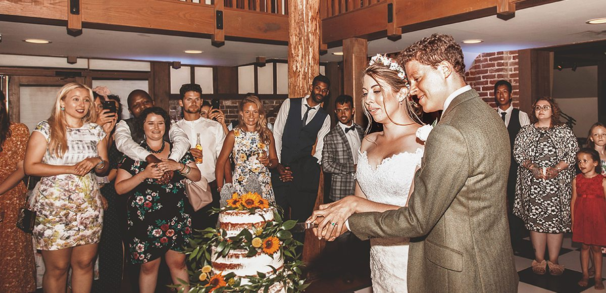 The couple cut their wedding cake in front of guests in the Mill Barn at Gaynes Park