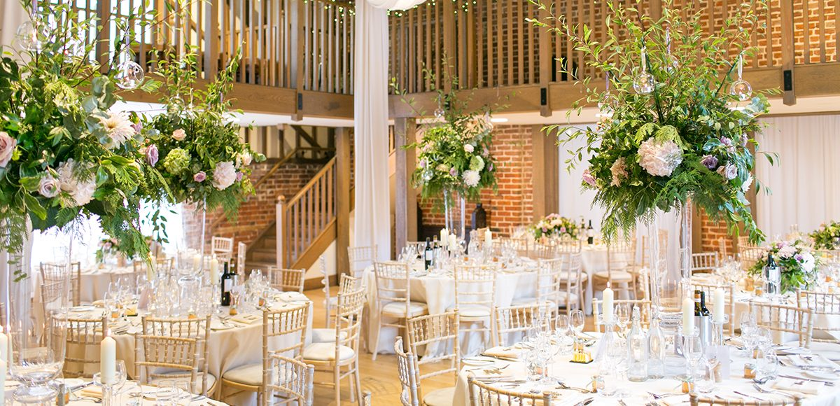 Tall wedding flower arrangements sit on tables in the Mill Barn at Gaynes Park for a beautiful spring wedding