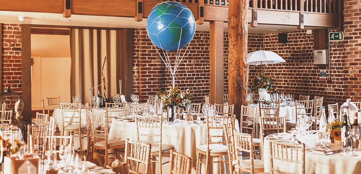 The Mill Barn at Gaynes Park is set up for a vintage inspired summer wedding reception