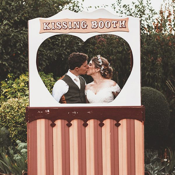 Newlyweds share a kiss in a kissing booth on their wedding day at Gaynes Park in Essex