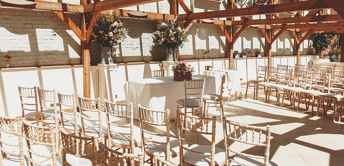 The Orangery at Gaynes Park is set up for a vintage inspired summer wedding ceremony