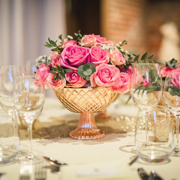 A bowl of brightly coloured roses are the perfect wedding table centrepiece for a spring wedding at Gaynes Park