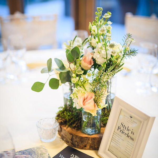 Roses in jars on a log slice are the perfect spring wedding table centrepiece at Gaynes Park