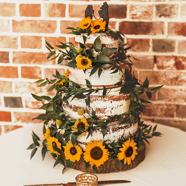 A semi naked wedding cake is decorated with sunflowers for this vintage inspired wedding at Gaynes Park