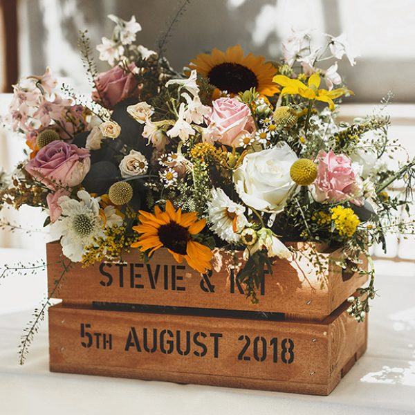 A wooden crate is filled with wild wedding flowers for the couples wedding ceremony at Gaynes Park