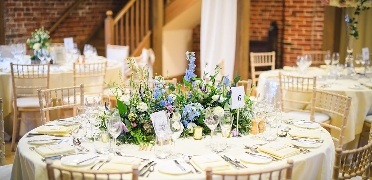 Wild spring table centrepieces work perfectly in the Mill Barn at Gaynes Park