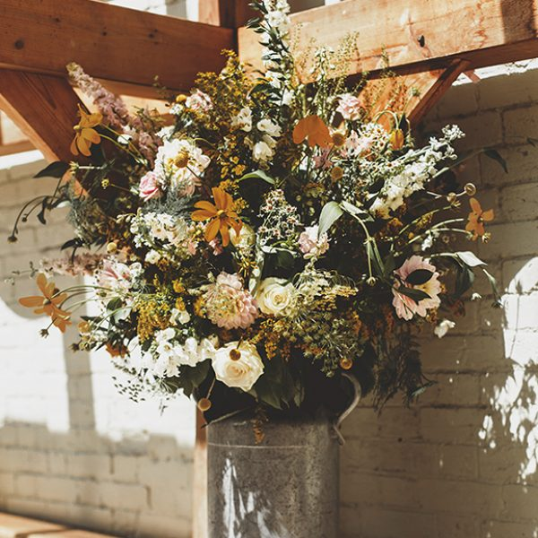 The couple chose wild wedding flowers for their vintage wedding day at Gaynes Park