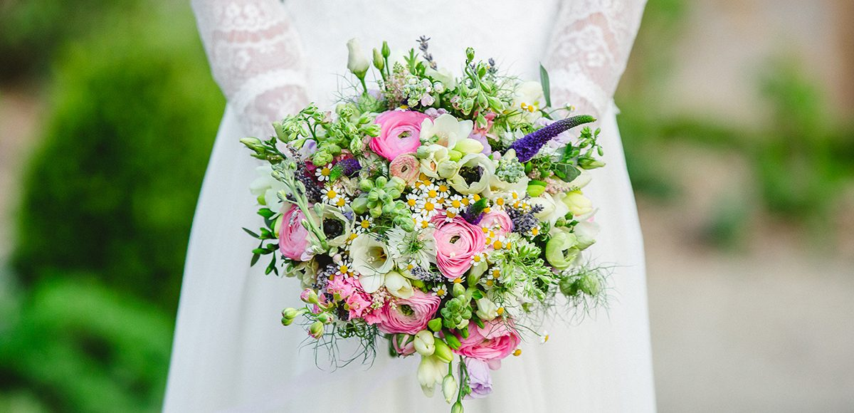 : A bride holds a wild flower bouquet for her spring wedding at Gaynes Park in Essex