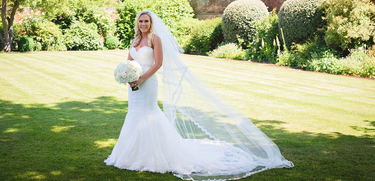 The bride holds a white wedding bouquet as she stands in her bridal gown in the walled garden at Gaynes Park