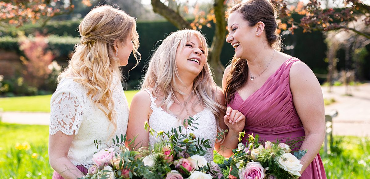 A bride enjoys a moment with her bridesmaids before her wedding ceremony at Gaynes Park