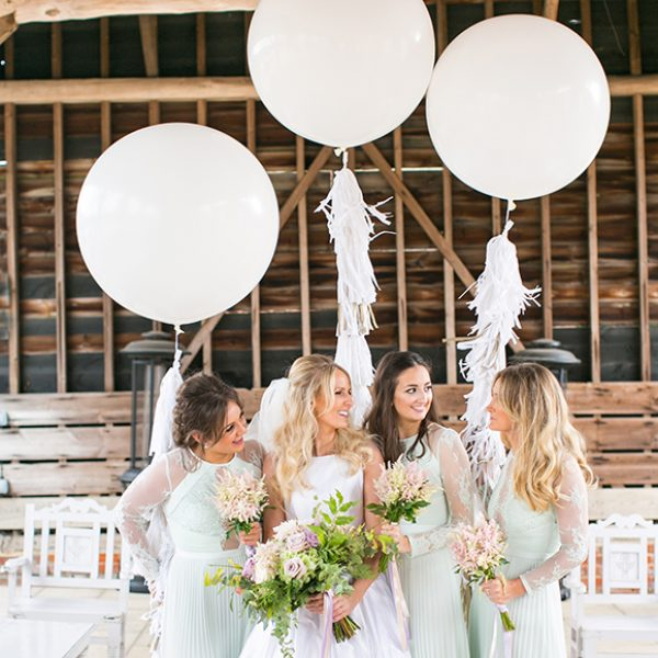 The bride stands with her bridesmaids in the Gather Barn at Gaynes park whilst giant white wedding balloons provide a beautiful backdrop