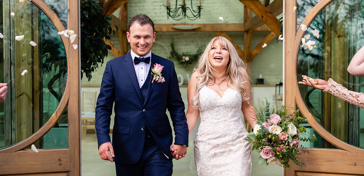 The bride and groom are showered in confetti after their wedding ceremony in The Orangery at Gaynes Park