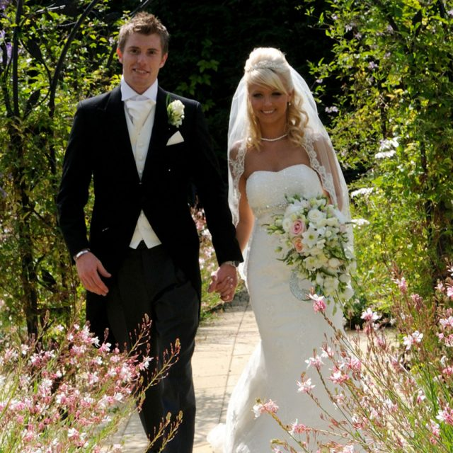 Bride and groom enjoying the summer flowers in the gardens of Gaynes Park