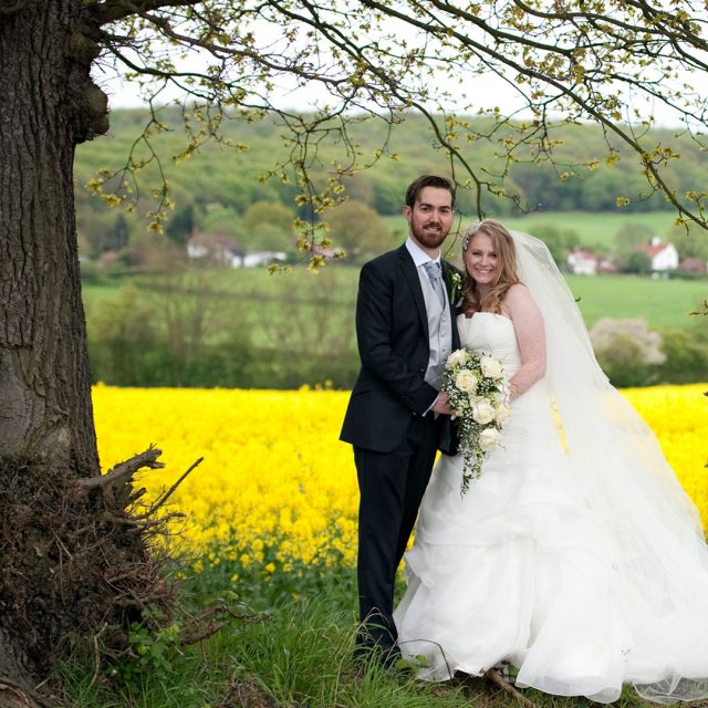 Bride and groom standing in front of yellow flower fields by Gaynes Park