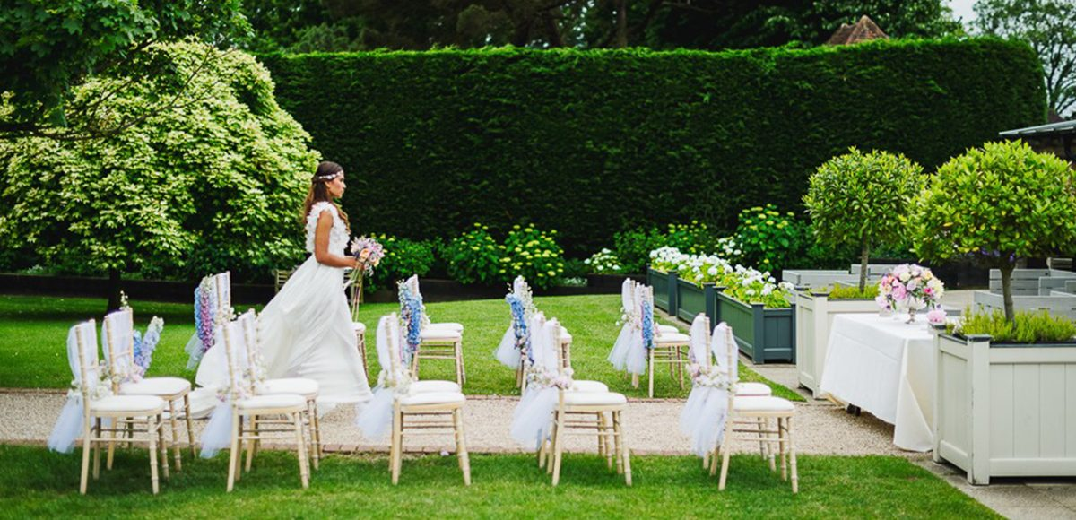 The bride walks down the aisle during an outdoor wedding ceremony at Gaynes Park