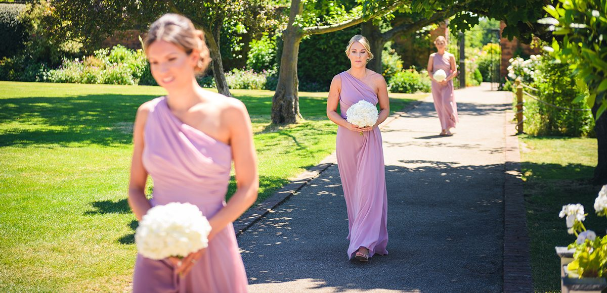 Bridesmaids walk down the beautiful garden aisle in the Walled Gardens at Gaynes Park