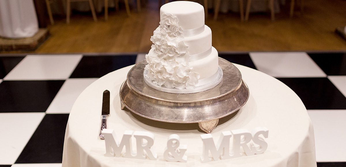 A traditional white wedding cake is the perfect finishing touch to a white wedding at Gaynes Park