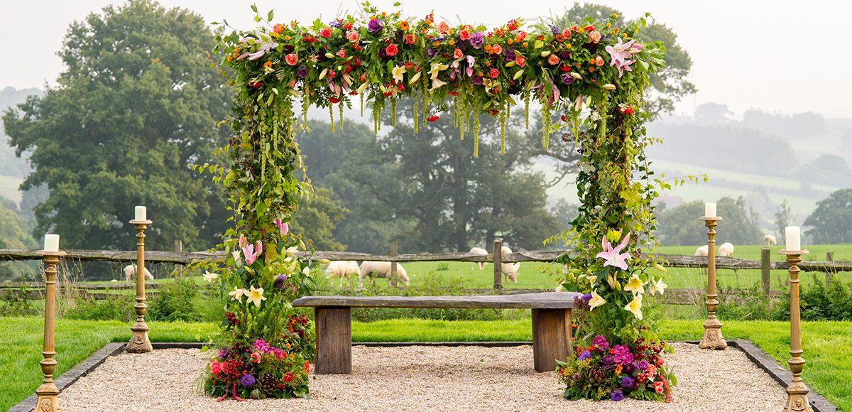 A floral wedding arch is the perfect wedding decoration for an outdoor wedding ceremony at Gaynes Park