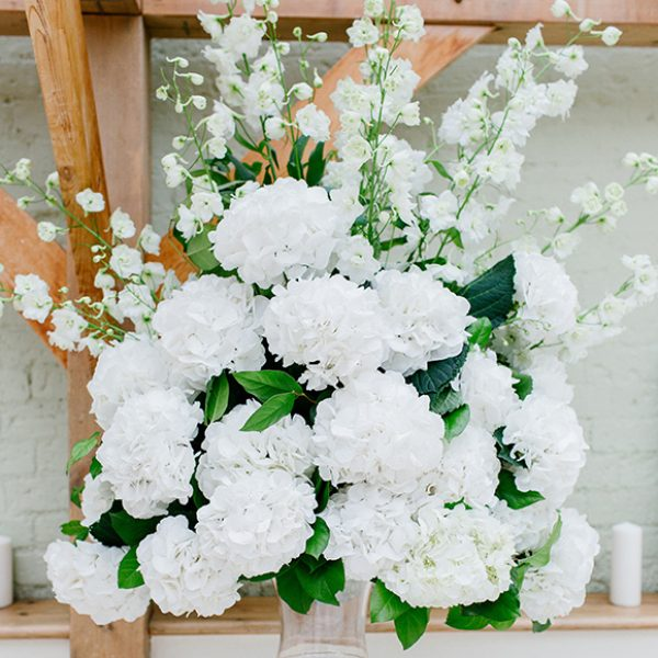 Large urns of white wedding flowers are perfect for an all-white wedding ceremony at Gaynes Park