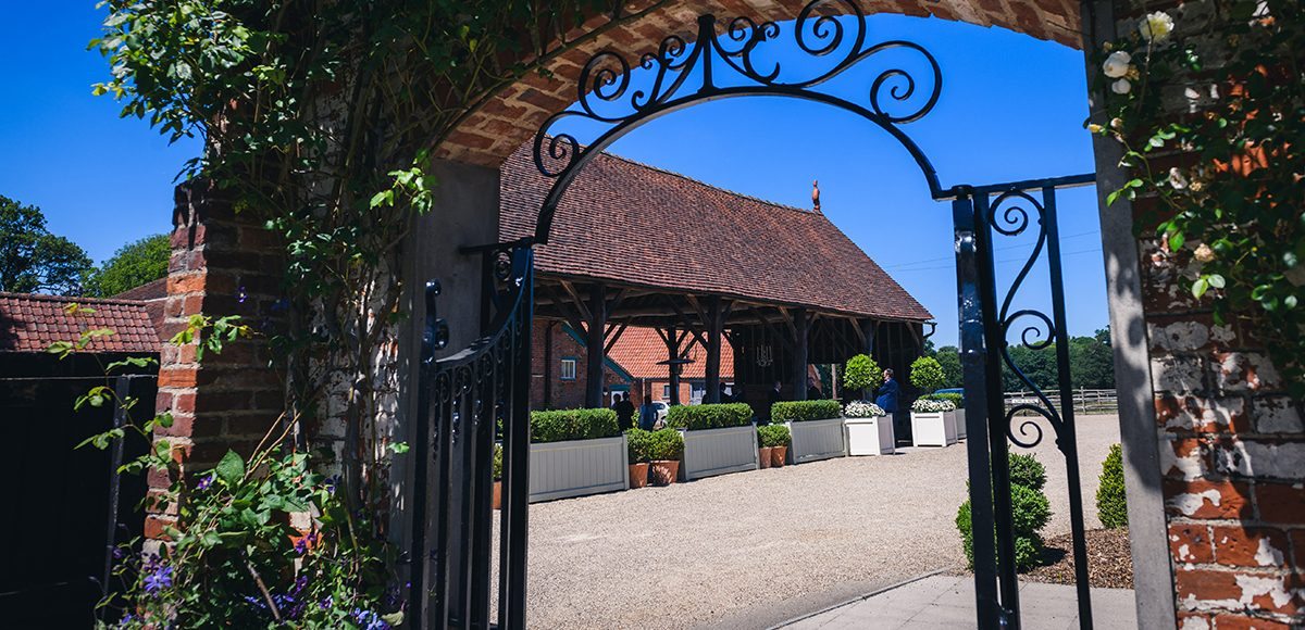 Looking through the gate from the walled garden you can see the Gather Barn at Gaynes Park wedding venue in Essex