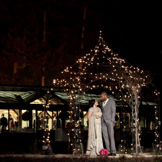 Bride and groom posing for photos at night after their barn wedding