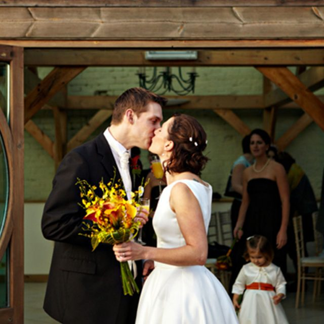Kathleen and Chris emjoying a quick kiss after their wedding ceremony at Gaynes Park in Essex