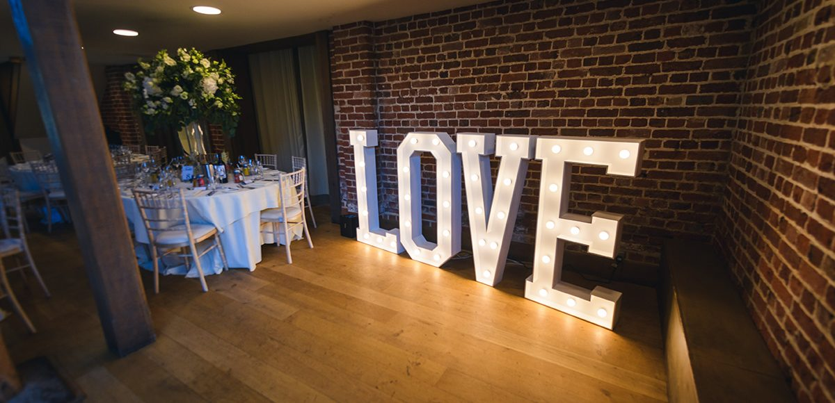 A couple chose giant light up love letters for their white wedding reception at Gaynes Park in Essex