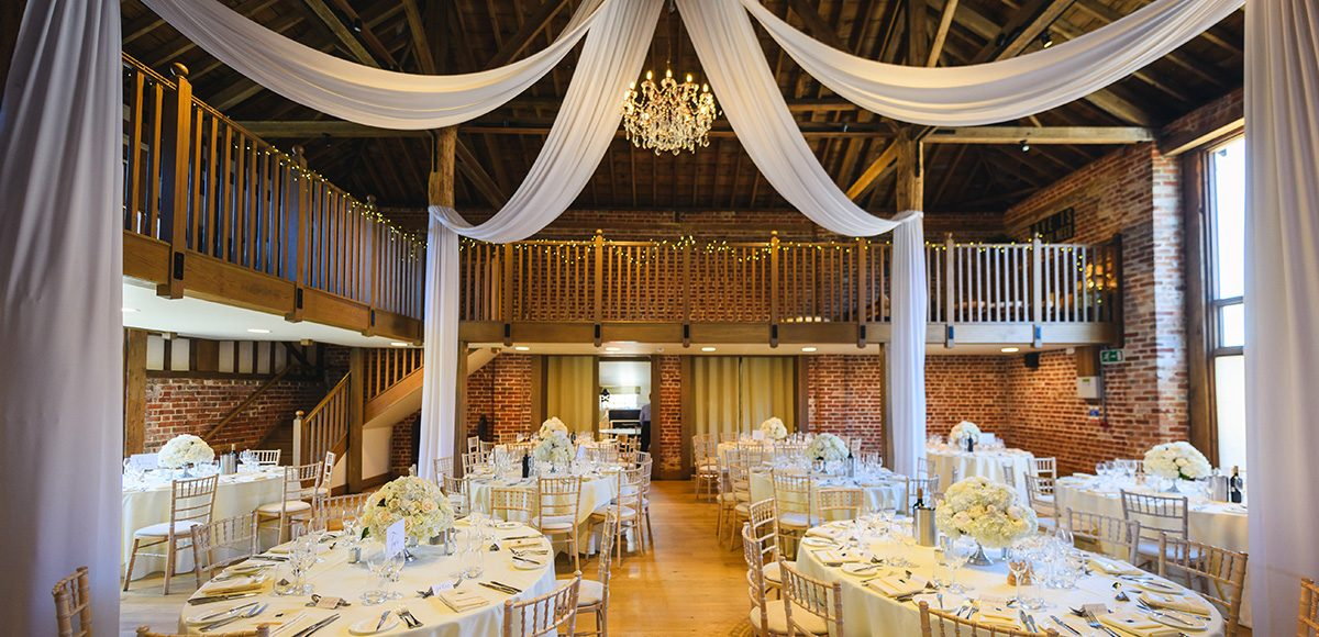 White drapes hung in the Mill Barn at Gaynes Park are perfect for an elegant white wedding reception