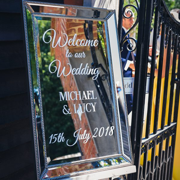 A mirror wedding sign welcomes guests to a wedding ceremony at Gaynes Park