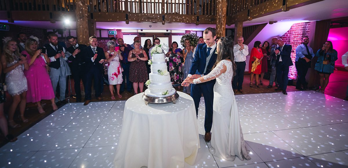 The newlyweds cut their white wedding cake during the evening reception at Gaynes Park