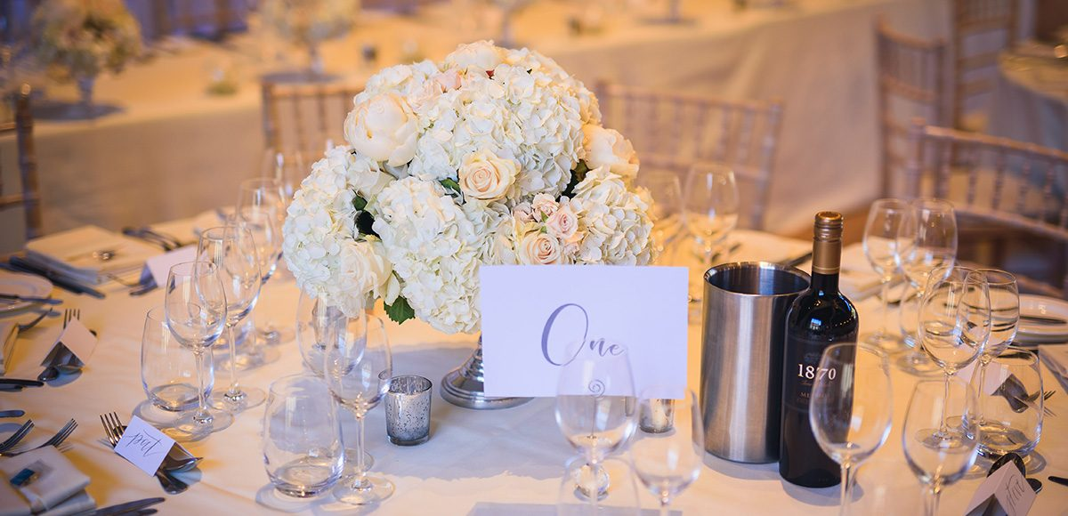 Clusters of white roses and hydrangeas make for elegant white table centrepieces in the Mill Barn at Gaynes Park