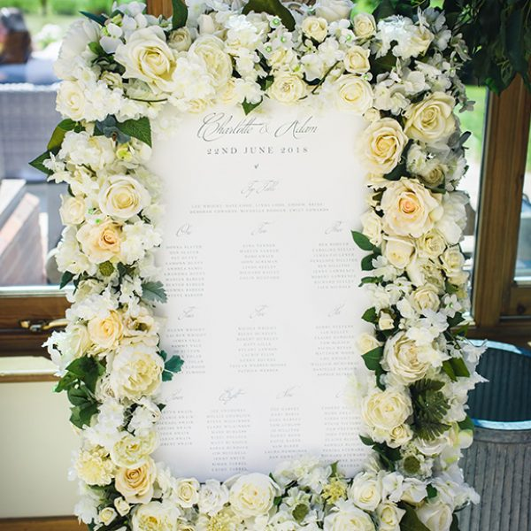 A table plan is decorated with white wedding flowers for an elegant wedding reception at Gaynes Park