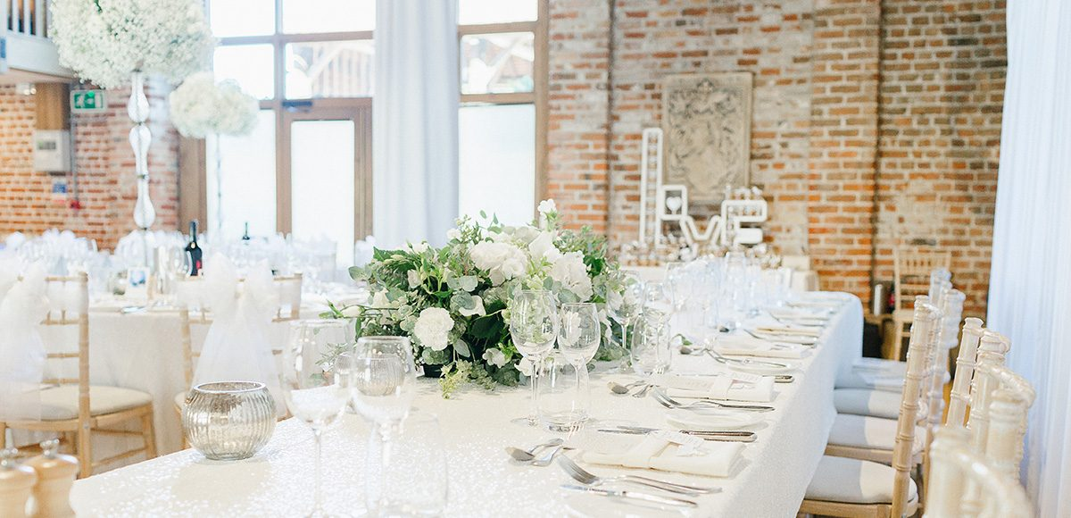 The top table in the Mill Barn at Gaynes Park is dressed for an all-white wedding reception