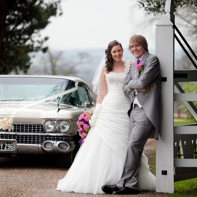 Bride and groom with their vintage wedding car at Gaynes Park