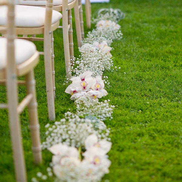 Floral posies line the wedding aisle for an outdoor wedding ceremony at Gaynes Park
