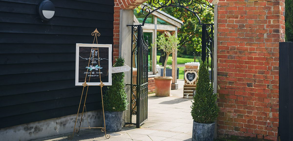 Wedding signs greet guests for an outdoor wedding ceremony at Gaynes Park